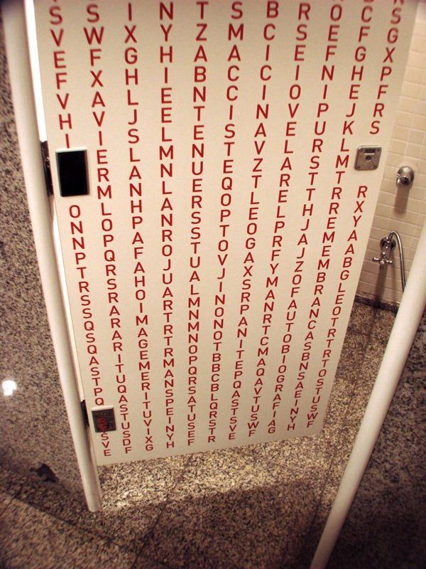 Porta de banheiro com a intervenção Caça-palavras (Poro)