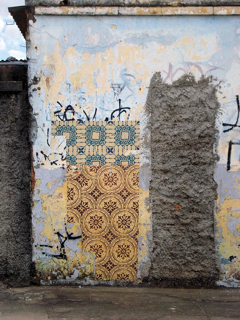Intervenção urbana Azulejos de Papel realizada pelo coletivo de arte Poro em muros de casas abandonadas