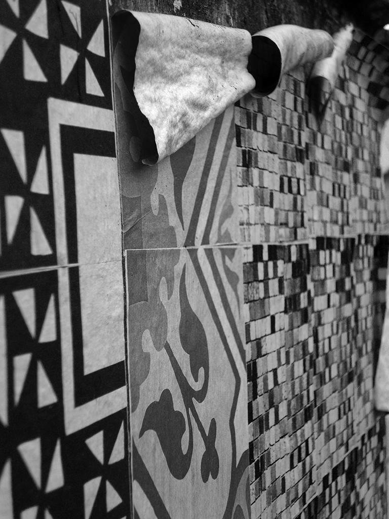 Detalhe dos Azulejos de Papel envelhecendo e descascando num muro de lote abandonado (Grupo Poro)